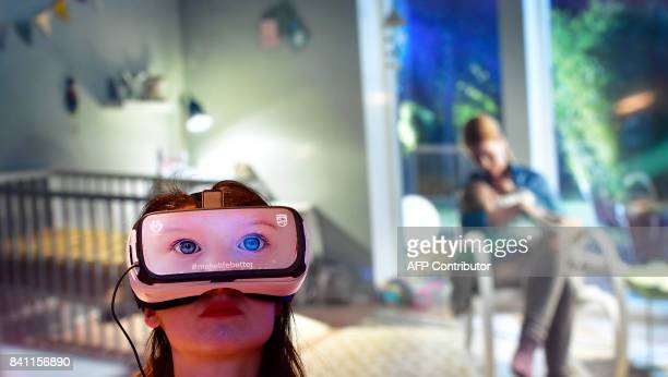 A fair worker presents VR glasses to promote baby surveillance systems at the booth of Philips at the IFA Consumer Electronics Fair in Berlin in...