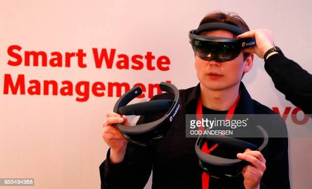 A fair worker tries out virtual reality glasses at the booth of telecommunications company Vodafone at the CeBIT technology fair in Hanover central...