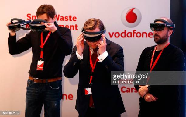 Fair workers try out virtual reality glasses at the booth of telecommunications company Vodafone at the CeBIT technology fair in Hanover central...