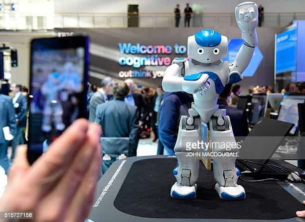 A fairgoer shoots a small dancing robot part of IBM's Watson AI department at the Digital Business fair CEBIT in Hanover central Germany on March 15...