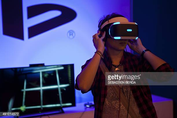 A fairgoer tests a VR headset for 3D gaming by Japanese publisher Sony Computer Entertainment during the Madrid Games Week 2015 in Madrid on October...