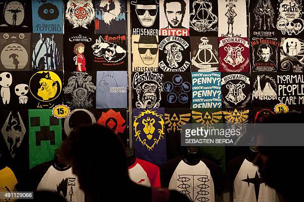 Fairgoers choose Tshirts featuring cinema TV series videogame comic manga designs and icons from a merchandising stand during the Madrid Games Week...