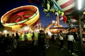 Fairgoers enjoy rides and games at dusk during the San Diego County Fair June 29 2005 in Del Mar California The fair features games rides live...