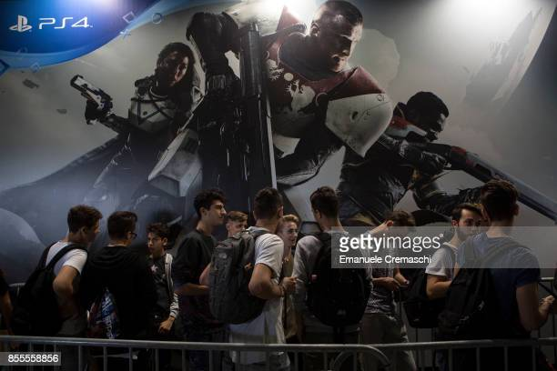 Fairgoers queue to play Destiny 2 at the PlayStation stand during the Milan Games Week on September 29 2017 in Milan Italy The Milan Games Week is...