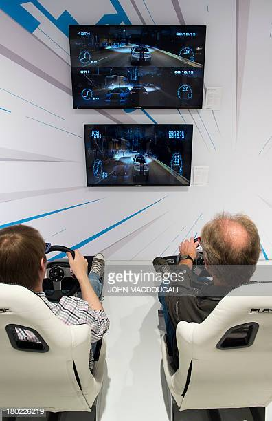 Fairgoers try out a car race simulator as they sit in a gaming suite at the Grundig stand during the 53rd IFA electronics trade fair in Berlin on...