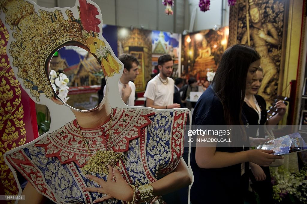 Fair-goers walk past a cardboard cut-out featuring a traditional Thai dancer at the Bangkok stand of the ITB International Travel Trade Fair in Berlin March 5, 2014. The ITB opens from March 5 to 9, 2014.