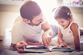 Father and his daughter reading book in bed.