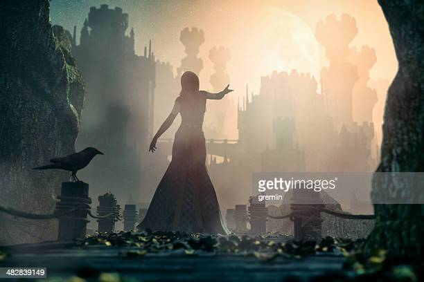 Princesse de conte de fées debout en face de l'ancien château de nuit