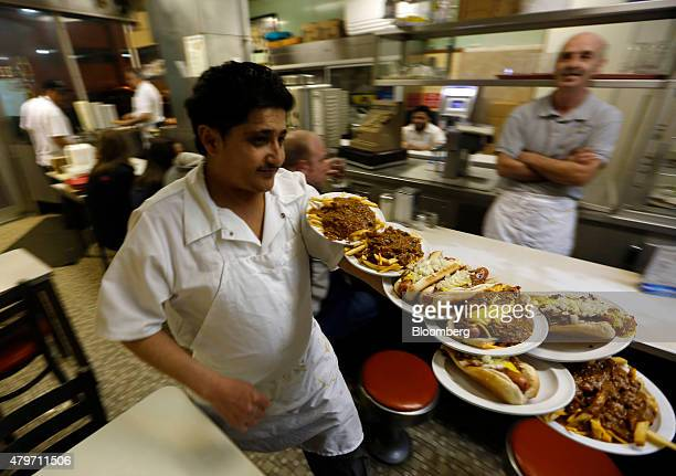 Faisal Ali delivers orders at Lafayette Coney Island in Detroit Michigan US on Saturday March 22 2014 Smothered in chili sauce mustard and onions the...