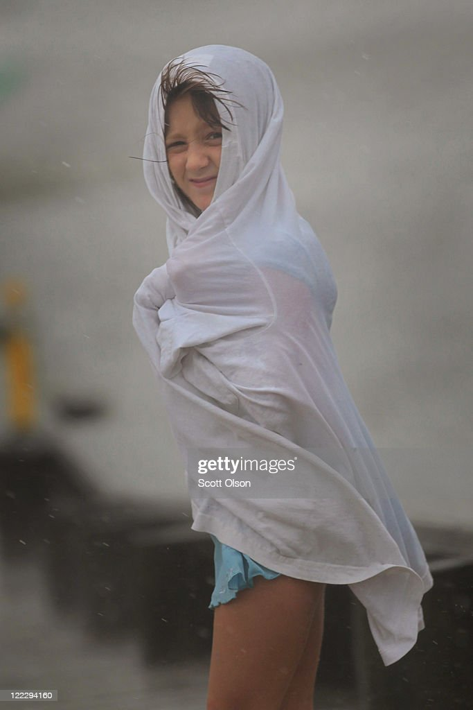 Faith Ann Mazik, 8, shields herself from the storm as she checks out Kitty Hawk Bay in Albemarle Sound during Hurricane Irene August 27, 2011 in Kill Devil Hills, North Carolina. Hurricane Irene hit Dare County, which sits along the Outer Banks and includes the vacation towns of Nags Head, Kitty Hawk and Kill Devil Hills, as a Category 1 hurricane around mid-day today.