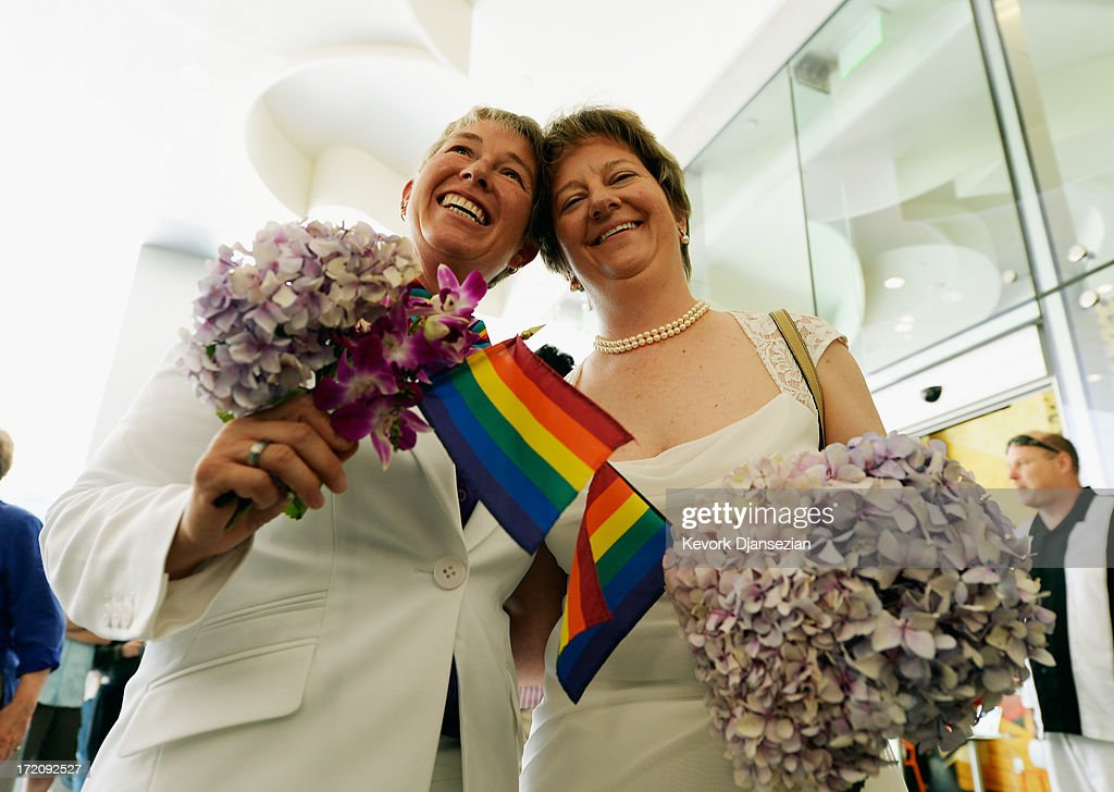 Faith Kassan, 46, and r Jennifer Ehrman, 43, hold wedding corsage with a rainbow colored flags before their are wed during a wedding ceremony on July 1, 2013 in West Hollywood, California. The U.S. Ninth Circuit Court of Appeals lifted California's ban on same-sex marriages just three days after the Supreme Court ruled that supporters of the ban, Proposition 8, could not defend it before the high court. California Gov. Jerry Brown ordered all counties in the state to begin issuing licenses immediately.