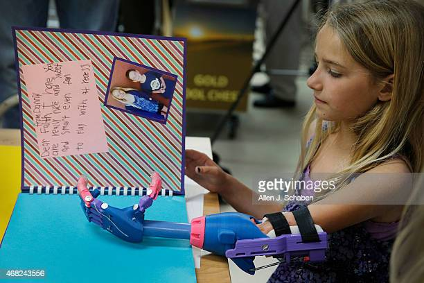 Faith Lennox of Lakewood uses her new left hand made by a 3D printer to hold a page as she reads inspiring letters her fellow first grade classmates...