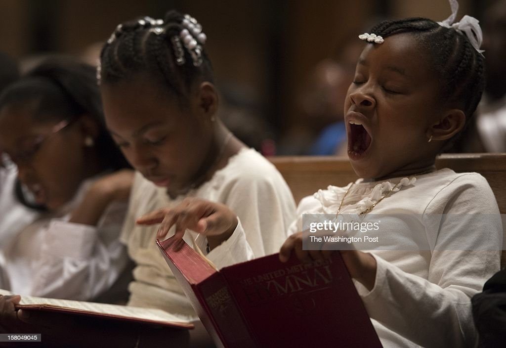 Faith Thomas and Alyssa Bruce (yawning), members of the Rhythm Starters, study Hymnal books prior to performing at First United Methodist Church of Hyattsville in MD on Dec. 8.