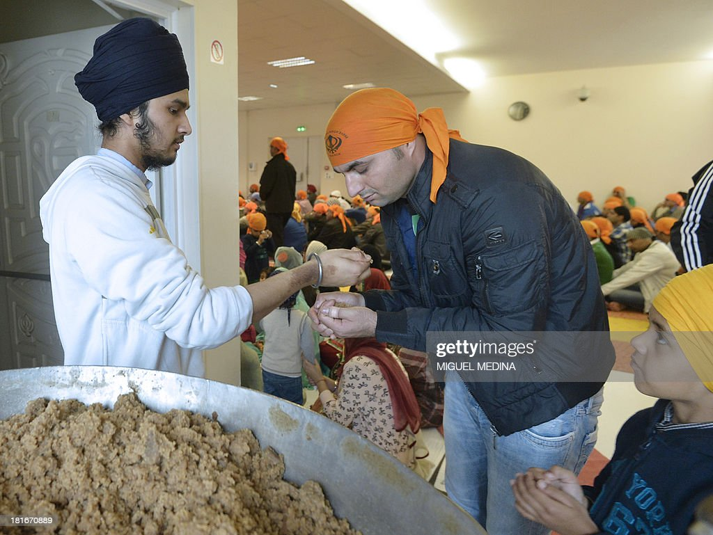 Faithful from the Paris Sikh community receive the 'parshad' (a wheat flour, butter and sugar semolina halva) on September 22, 2013 at the largest gurdwara or Sikh temple in France, located in the Paris suburb of Bobigny. France's Sikh community is ramping up a campaign for the turban to be allowed in state-funded schools amid moves to reinforce a 2004 law banning pupils from sporting religious symbols. The contentious issue pits the cherished French principle of secularity in public life and institutions against the essence of the Sikh religion, which requires followers to keep long hair as a mark of their faith and piety and a turban to cover the tresses, worn as a bun on the top of the head.