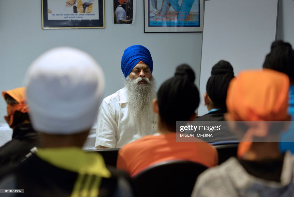 A faithful from the Sikh community prays with children during a meditation class on September 22, 2013 at the largest gurdwara or Sikh temple in France, located in the Paris suburb of Bobigny. France's Sikh community is ramping up a campaign for the turban to be allowed in state-funded schools amid moves to reinforce a 2004 law banning pupils from sporting religious symbols. The contentious issue pits the cherished French principle of secularity in public life and institutions against the essence of the Sikh religion, which requires followers to keep long hair as a mark of their faith and piety and a turban to cover the tresses, worn as a bun on the top of the head.