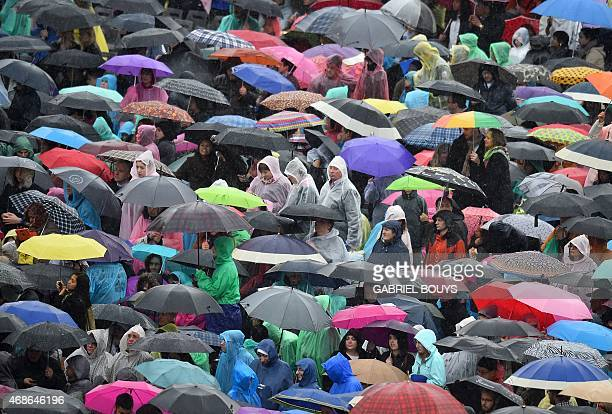 Faithful gather under heavy rain for the Easter Mass at St Peter's square on April 5 2015 in Vatican Pope Francis condemned yesterday indifference...