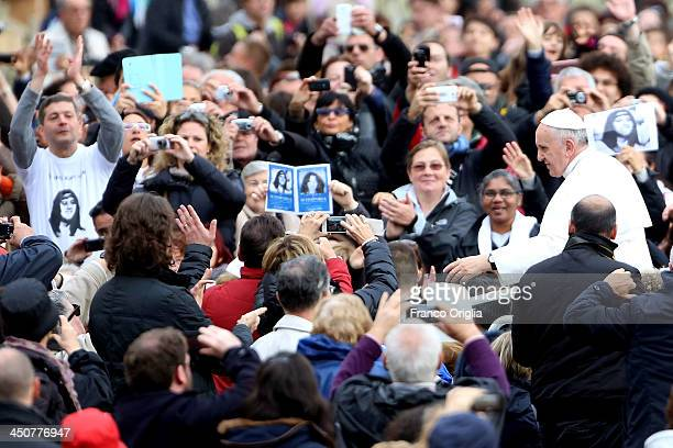 Faithful hold banners showing the face of Emanuela Orlandi as Pope Francis arrives in St Peter's square for his weekly audience on November 20 2013...