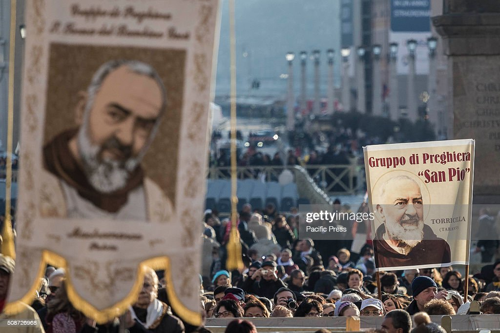 Faithful hold portraits of Padre Pio as they gather in St. Peter's Square before the arrival of Pope Francis for an audience to the Padre Pio Prayer Groups at the Vatican. Padre Pio became famous for bearing the stigmata, which are the marks of Christ, for most of his life, thereby generating much interest and controversy. He was both beatified (1999) and canonized (2002) by Pope John Paul II.