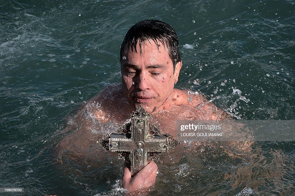 A faithful holds a cross after retrieving it from the sea during the blessing of the waters marking the Epiphany Day in the city of Volos, in central Greece's region on January 6, 2013.