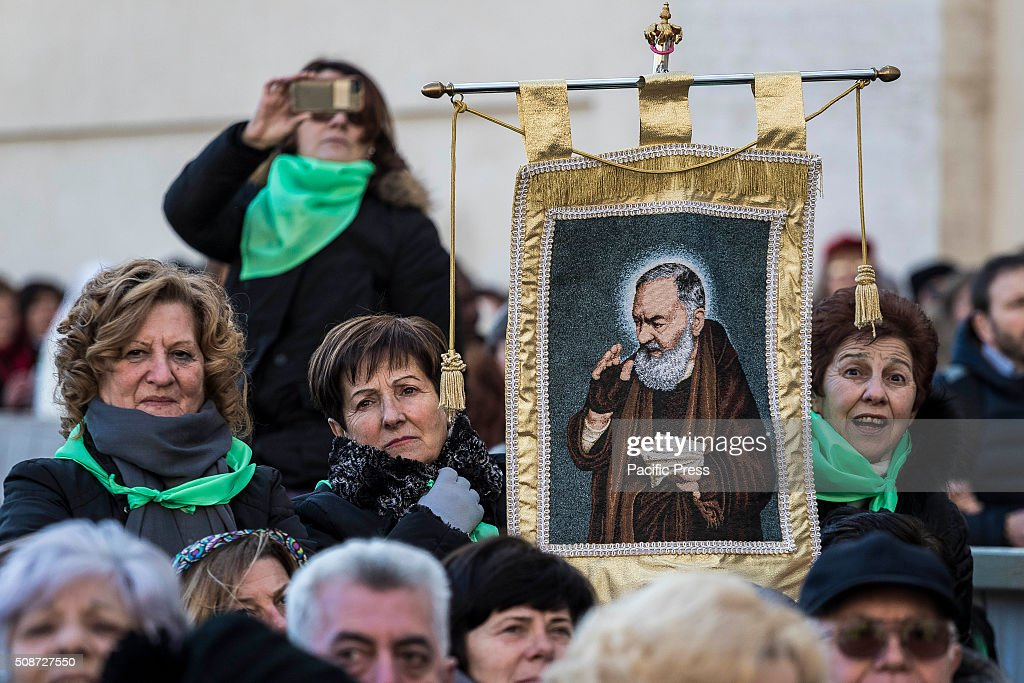 A faithful holds a portrait of Padre Pio as he gather in St. Peter's Square before the arrival of Pope Francis for an audience to the Padre Pio Prayer Groups at the Vatican. Padre Pio became famous for bearing the stigmata, which are the marks of Christ, for most of his life, thereby generating much interest and controversy. He was both beatified (1999) and canonized (2002) by Pope John Paul II.