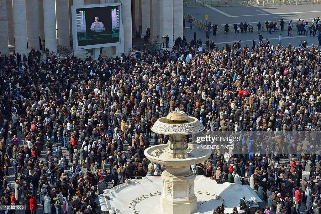 Faithful lok at Pope Benedict XVI on a giant screen on St Peter's square during the Angelus prayer led by Pope Benedict XVI from the window of his appartments on February 17, 2013 at the Vatican. The Vatican the day before said it could speed up the election of a new pope as lobbying for Benedict XVI's job intensified amid speculation over who had the best chance to succeed him. AFP PHOTO / VINCENZO PINTO