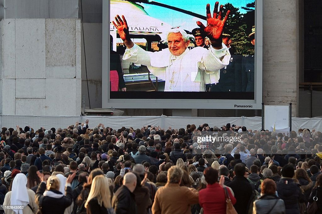Faithful look at a giant screen on St Peter's square showing Pope Benedict XVI boarding a helicopter at the Vatican on February 28, 2013 at the Vatican. Pope Benedict XVI boarded a helicopter to fly to the papal summer residence of Castel Gandolfo outside Rome, where he will stay until his powers formally expire at 1900 GMT. AFP PHOTO / ALBERTO PIZZOLI