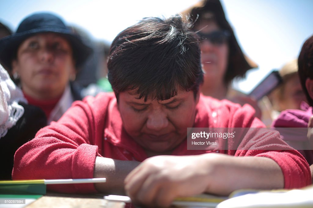 Faithful prays after receiving the communion wafer during a mass for the people at Ecatepec on February 14, 2016 in Ecatepec, Mexico. Pope Francis is on a five days visit in Mexico from February 12 to 17 where he is expected to visit five states.