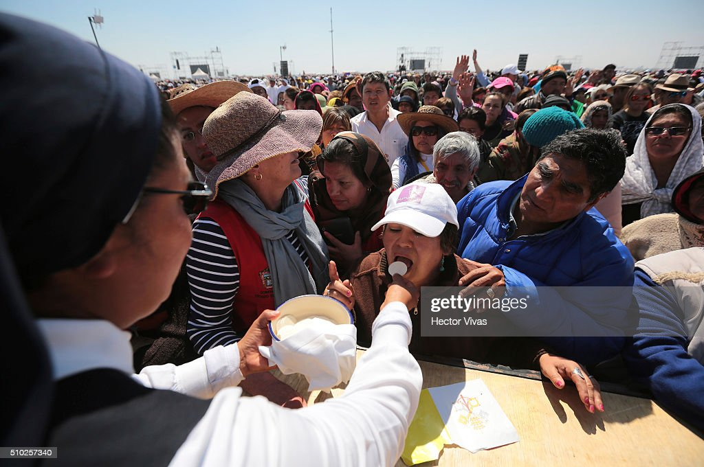 Faithful receives the communion wafer during a mass at El Caracol on February 14, 2016 in Ecatepec, Mexico. Pope Francis is on a five days visit in Mexico from February 12 to 17 where he is expected to visit five states.