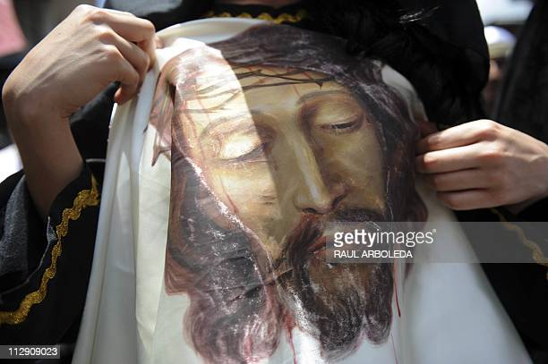 A faithful shows an imitation of the Turin Shroud during the Good Friday procession along a street in Medellin Antioquia department Colombia on April...