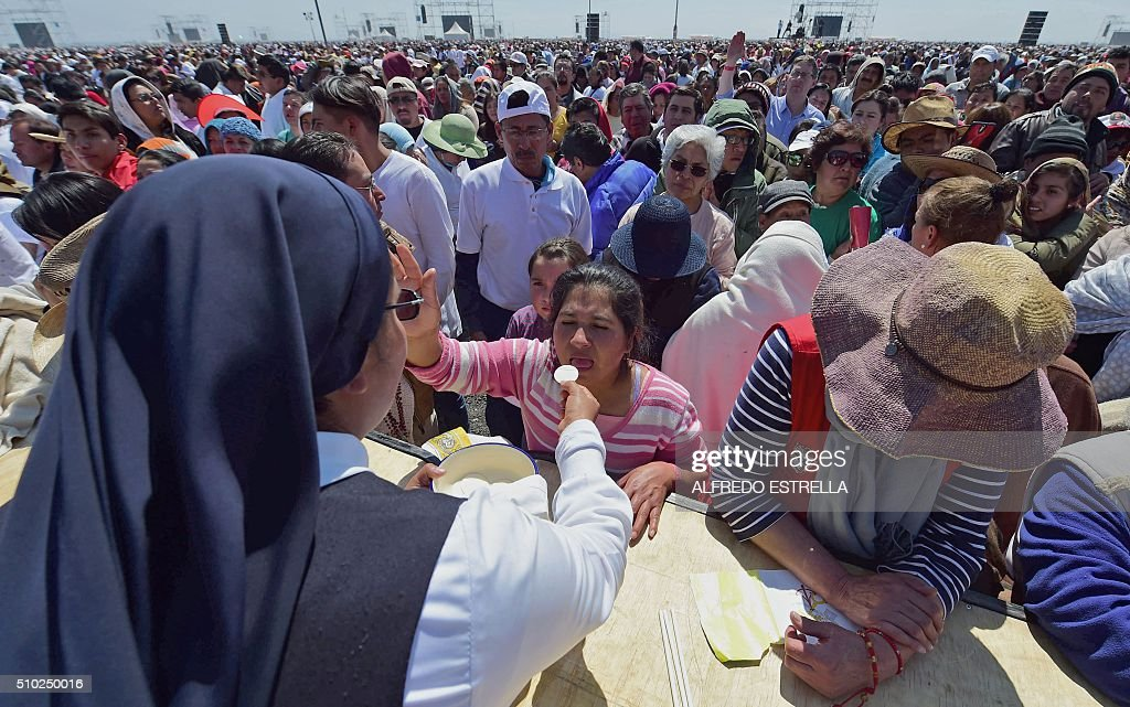 Faithful take the communion during an open-air mass officiated by Pope Francis in Ecatepec, near Mexico City, on February 14, 2016. Pope Francis urged Mexicans on Sunday to turn their country into a land of opportunity where there is no need to emigrate or mourn victims 'of the merchants of death.' AFP PHOTO/ALFREDO ESTRELLA / AFP / ALFREDO ESTRELLA