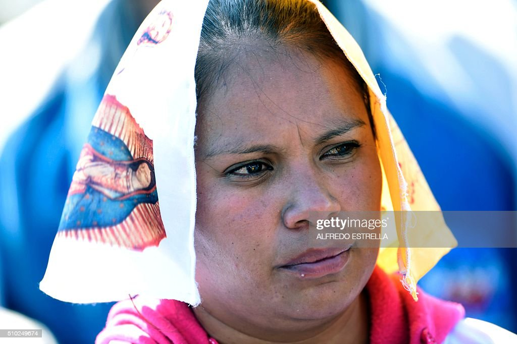 A faithful takes part in an open-air mass officiated by Pope Francis in Ecatepec, near Mexico City, on February 14, 2016. Pope Francis urged Mexicans on Sunday to turn their country into a land of opportunity where there is no need to emigrate or mourn victims 'of the merchants of death.' AFP PHOTO/ALFREDO ESTRELLA / AFP / ALFREDO ESTRELLA