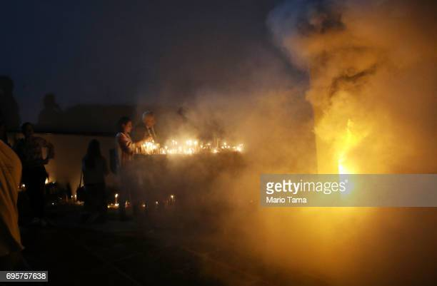 Faithful worship with candles at the annual feast of Saint Anthony of Padua as a small fire from candles burns at a statue of the saint at the Santo...