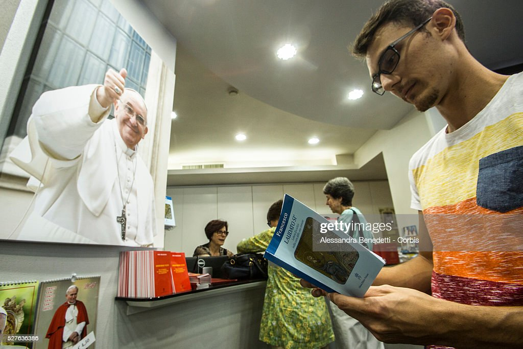 faithfuls buying copies of pope francis encyclical letter laudato si on care for our