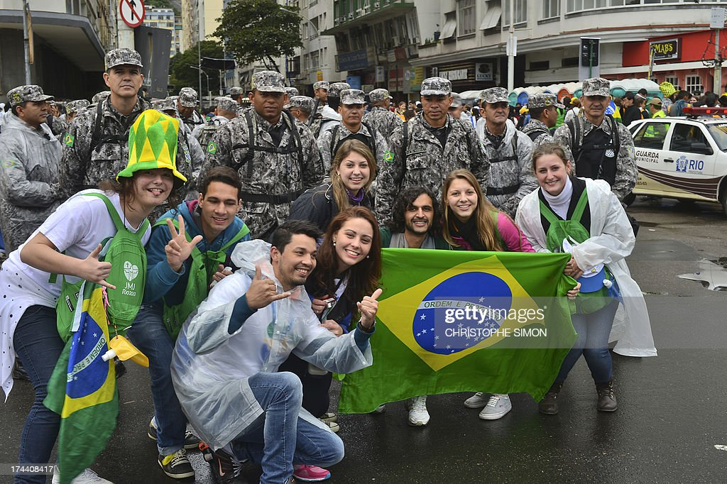 Faithfuls pose next to policemen holding a Brazilian flag on their way to Copacabana beach where in the evening Pope Francis will be officially welcomed by crowds of young Catholics attending World Youth Day (WYD) on July 25, 2013. Pope Francis urged young Brazilians not to despair in the battle against corruption Thursday as he addressed their country's political problems in the wake of massive protests.
