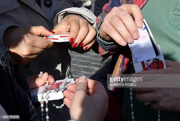 Faithfuls unbox rosaries during Pope Francis' Sunday Angelus from the window overlooking StPeter's square on November 17 2013 at the Vatican The Pope...