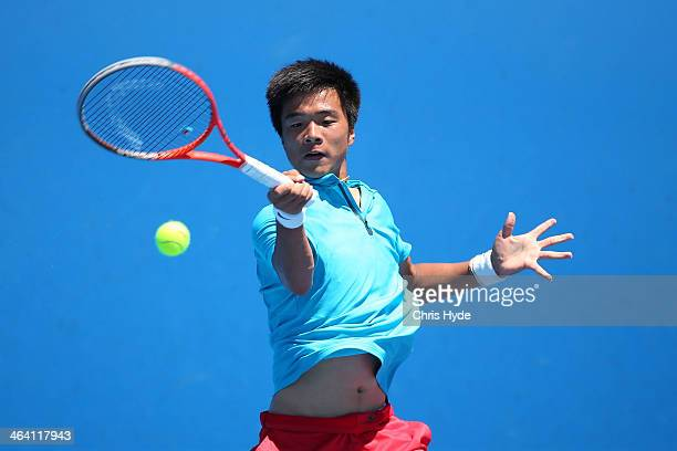 Fajing Sun of China plays a forehand in his second round junior boys' match against Daniil Medvedev of Russia during the 2014 Australian Open Junior...