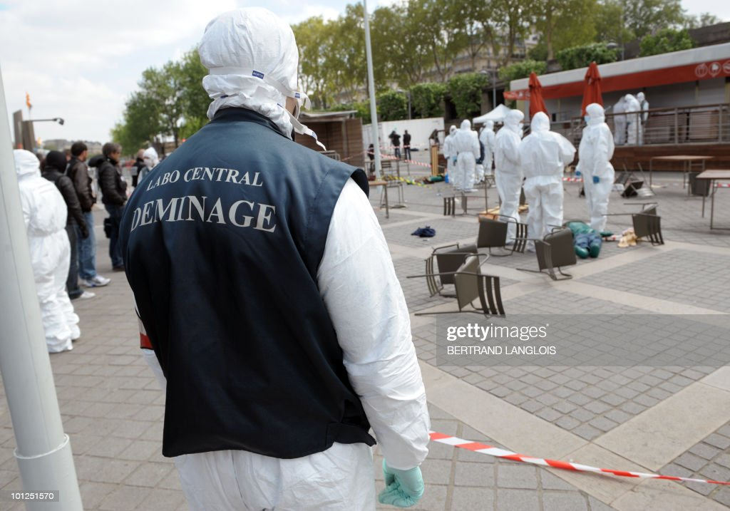 A fake body lies on the bank of the River Seine as policemen wearing NBC attend a multi attacks exercise on May 4, 2010 near the Eiffel Tower in Paris. Intitled 'Omega 2010', the exercise is organised by the Secretary General for the Zone of Defence and Security of the Prefecture of Police in several places in Paris and aims to train police forces to multi attacks.