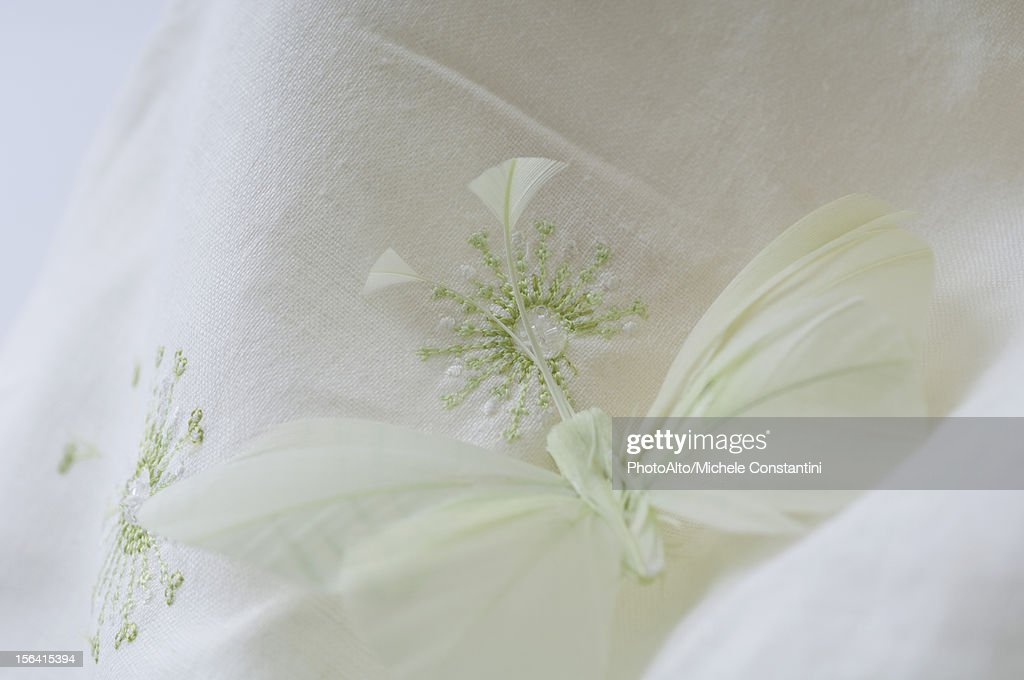 Fake butterfly resting on embroidered fabric : Stock Photo