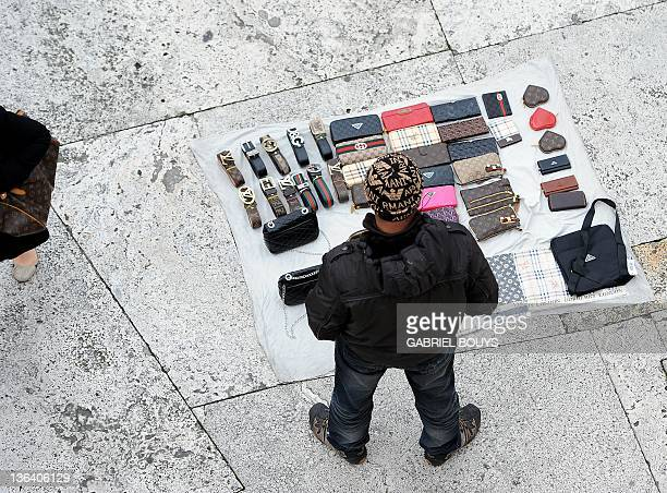 Fake designer bags and belts for sale are displayed by an unidentified sailor near the Spanish steps in Rome on January 4 2012 Handbags are displayed...