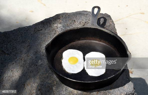 Fake eggs in a frying pan are displayed near a 134foothigh electronic sign that gives the temperature on July 23 2014 in Baker California The...
