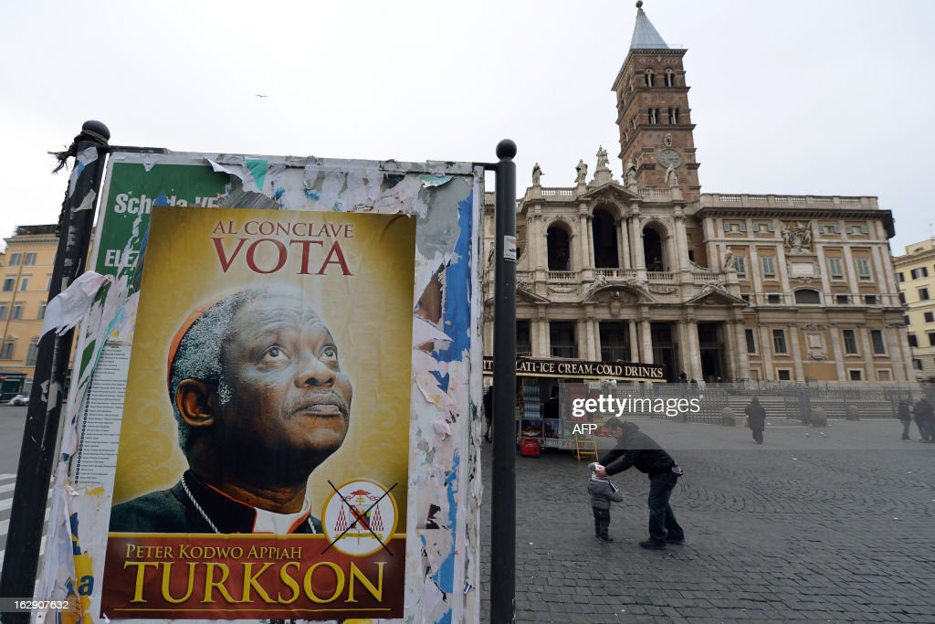 A fake electoral placard showing Ghana's Cardinal Peter Turkson, seen by some as Africa's top candidate to become the next pope and reading 'during the conclave, vote Turkson' is displayed in front of the Santa Maria Maggiore basilica on March 1, 2013 in Rome. Catholic cardinals from around the world were summoned Friday to meetings that will set a date for a conclave to elect a new pope, the day after Benedict XVI's historic resignation. AFP PHOTO / ALBERTO PIZZOLI