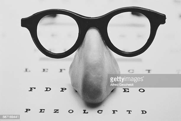 A fake nose and spectacles on top of an optician's eye chart 1993