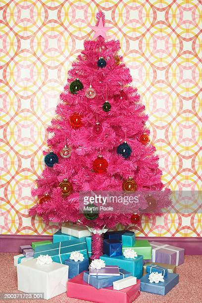 Fake pink Christmas tree surrounded by gifts