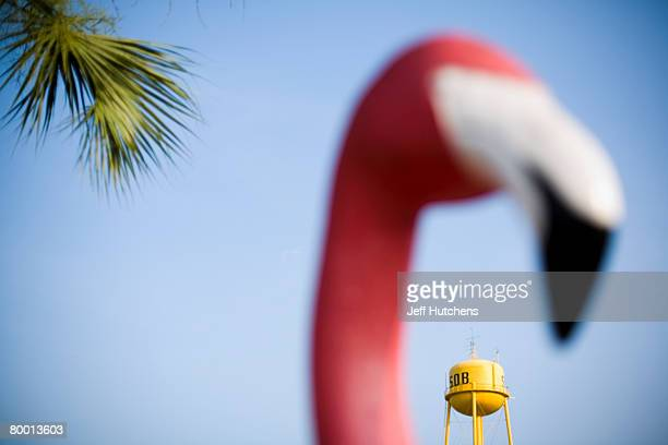 A fake pink flamingo stands in the foreground as a South of the Border water tower and a palm tree compose the background at South of the Border on...