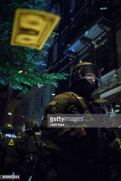 Fake US currency cascades from an apartment window onto riot police below during the ÒWelcome to HellÓ antiG20 protest march on July 7 2017 in...