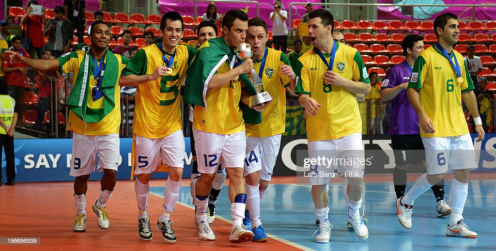 Falcao of Brazil kisses the trophy and celebrates with team mates after winning the FIFA Futsal World Cup Final at Indoor Stadium Huamark on November 18, 2012 in Bangkok, Thailand.