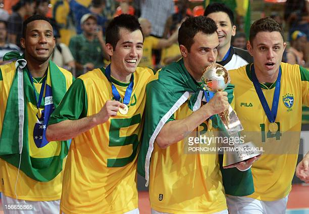 Falcao of Brazil kisses the winner's trophy as he celebrates with teammates during the trophy ceremony of the FIFA Futsal World Cup 2012 in Bangkok...