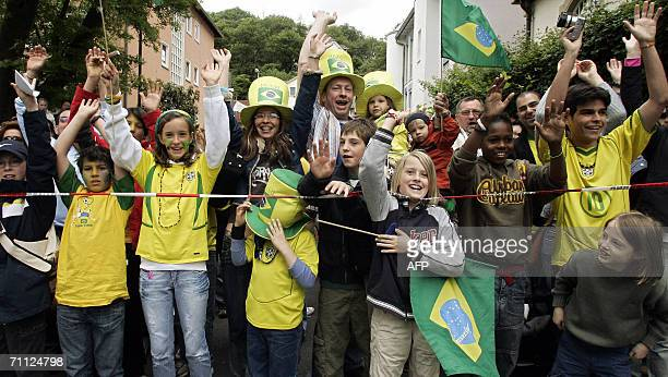 Supporters of Brazilian football team try out with a Mexican wave outside the hotel where Brazil's team are hosted in Falkenstein Germany 05 June...
