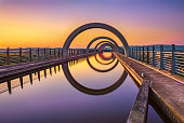 Falkirk Wheel at sunset. Falkirk Wheel is a rotating boat lift in Scotland and connects the Forth and Clyde Canal with the Union Canal. Long exposure.