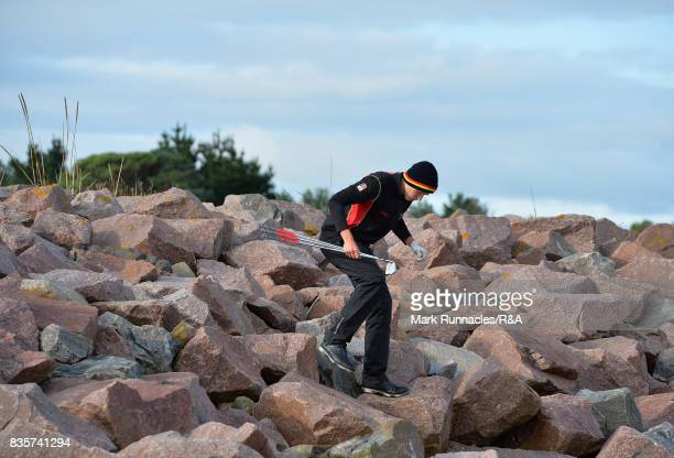 Falko Hanisch of Germany carefully climbs down the rocks onto the beach running along the right of the first fairway to plays his second shot to the...